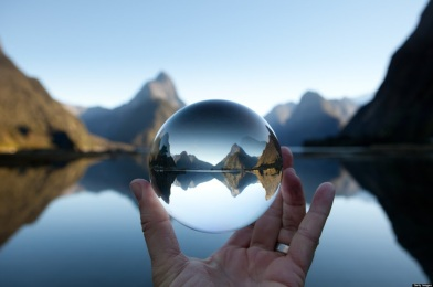 Man holding crystal ball in landscape